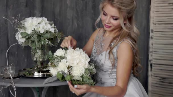 Beautiful blond woman model with a wedding dress sit on a chair with a bouquet of flowers on a gray background