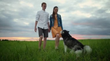 Loving couple playing with dog at the beach. Concept about love, animal and lifestyle