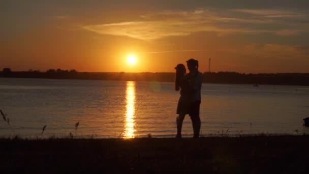 szenvedélyes pár tartja egymást a tengerparton naplementekor.