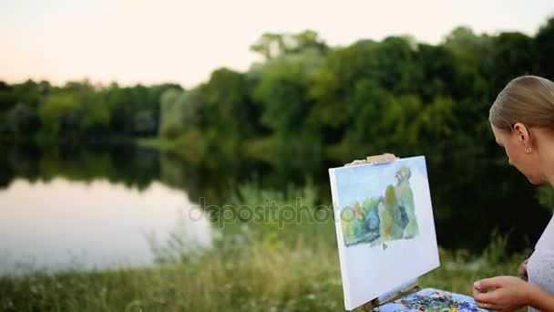 mladý umělec obraz obrázek v parku s štětce a barvy sedí romantické jezero a městských objektů v pozadí. Ultra široký úhel pohledu