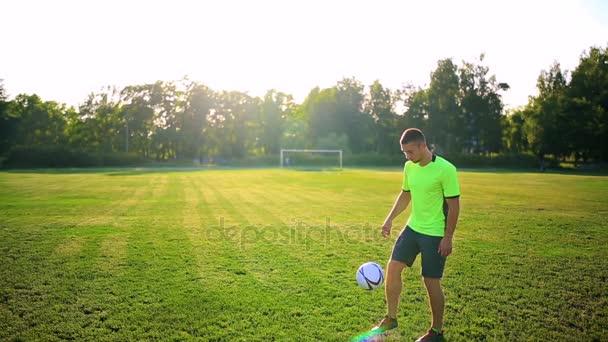 Sport, fotbal a lidé - fotbalista hrající a žonglování s míčem na hřišti