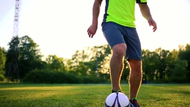 Detail nohy a chodidla fotbalista v akci na sobě černé boty běh a driblování s míčem na zelené trávě hřiště izolované na černém pozadí