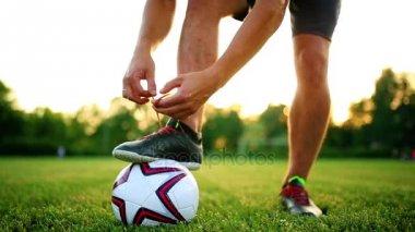 Profesionální fotbalista na tréninku vázání tkaničky do bot. Detail s míčem