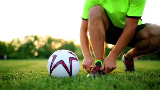 Profesionální fotbalista na tréninku vázání tkaničky do bot. Detail s míčem.