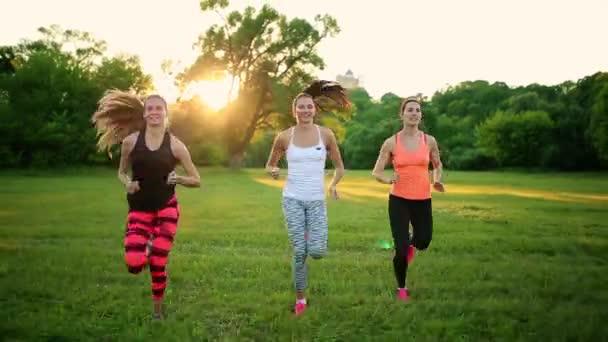 Skupina zdravých dívek běží venku při západu slunce s odlesk objektivu.