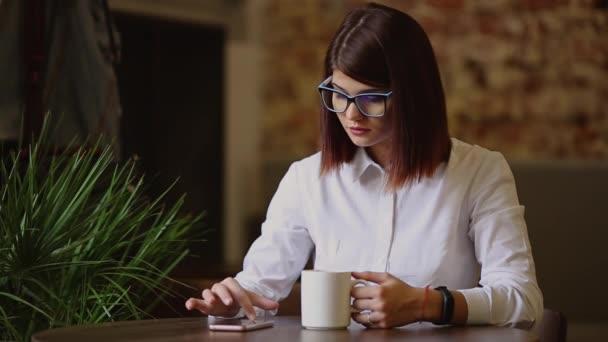 Simpatic barna, közelkép szemüveg. Italok, illatos kávé és használ egy mozgatható telefon tárcsázza a szöveges üzenetek, Hírek órák, fejtetőre keresztül képeket, kommunikál a szociális háló.