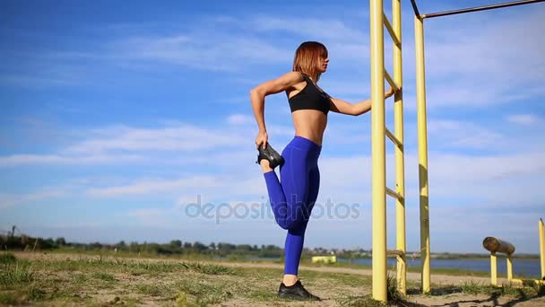 La ragazza nei leggings blu impasta piedi su una scala verticale. Allunga i muscoli e preparando per attività outdoor su sfondo blu cielo.