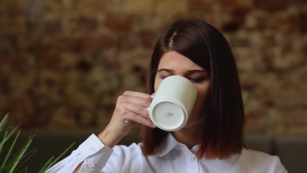 Young girl sitting in the cafe, drinking cofee and talking with someone.