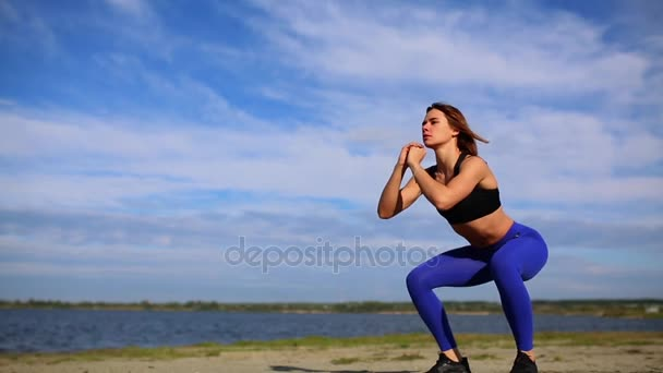 young beautiful sexy woman doing sports on beach, sunrise, morning exercises, listening to music on headphones, healthy lifestyle, work out, doing sit-ups