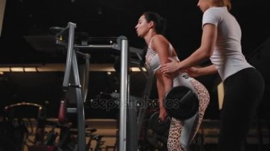 Personal female trainer in white t-shirt helps to do the exercise deadlift female female client with long dark hair. Exercising in a gym.