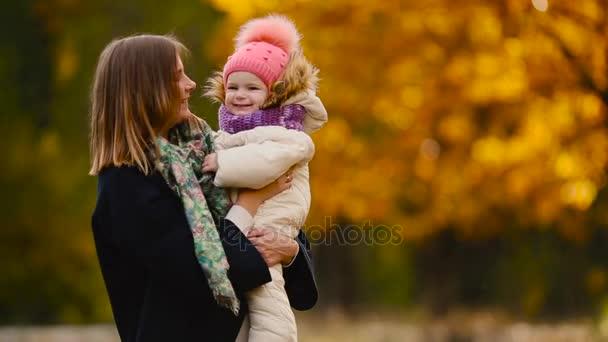 na podzim, kdy žluté listy kolem Maminka a dívka si hraje s javorové listy a smíchu. Maminka objímá a hraje si s dcerou na podzim. Bokeh a sluneční světlo.