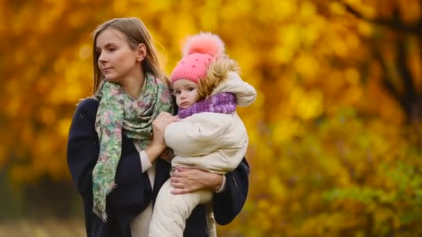 in autumn, when yellow leaves around mom and girl playing with maple leaves, laughing and smiling. Mom hugs and plays with my daughter in the fall. Bokeh and sunlight.