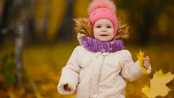 Detailní portrét holčičku stojící s javorový list a při pohledu na fotoaparát, usmíval se a mluvit s mámou.