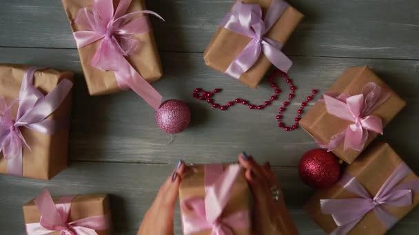 Plán shora dolů. Plně viditelná tabulka s dekorací. Ženské ruce dát a finalizovat vánoční dárek zabalený v papíru craftool na dřevěný stůl. Bandážování páskou a svázané v přídi