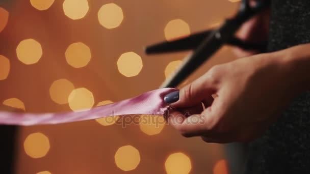 Gros plan des mains féminines, ont coupé le ruban pour la fabrication de  cadeaux faits à la main pour Noël à vos proches. Sur le fond de guirlandes  de ... cd75a72f066