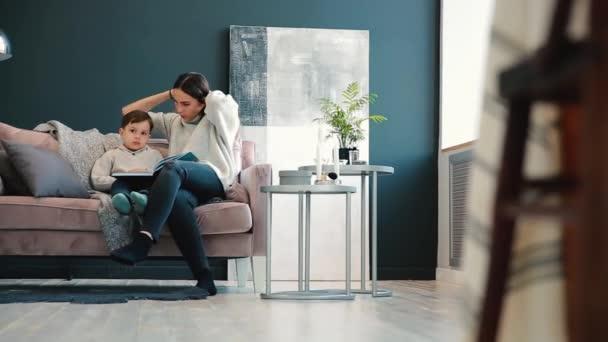 Krásná mladá matka sedí na pohovce ve vašem domě obývacího pokoje čte syna příběh v uchu a naučit se číst malého chlapce.