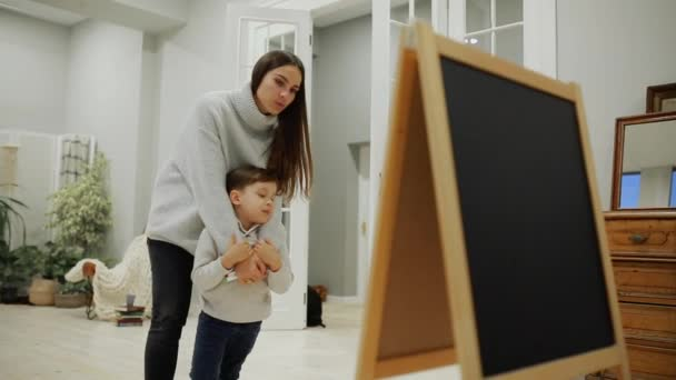 Kis fiú, az anya a nappali házában festeni a táblán jelölőkkel egy rajz childs. Szabadidős boldog család. Iskola előtti oktatás