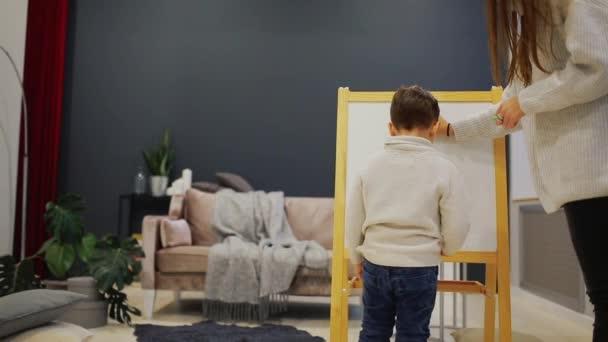 Ragazzino con la mamma nella sua casa di soggiorno dipingere sulla ...