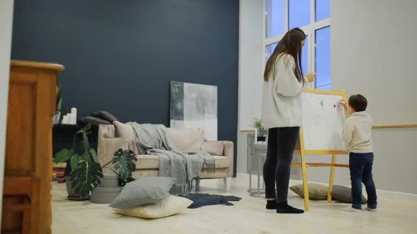 Dipingere Soggiorno : Ragazzino con la mamma nella sua casa di soggiorno dipingere sulla