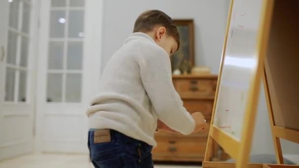 Malého chlapce v obývacím pokoji domu kreslit na tabuli se značkami dětské kresby. Předškolní vzdělávání. detail