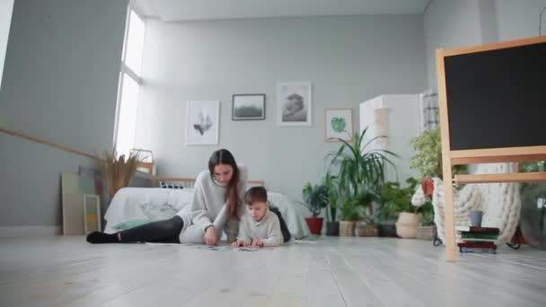 Matka s dítětem v bílý interiér svého domova k sbírat puzzle s jeho mladého syna. Šťastná rodina, vzdělávací hry.