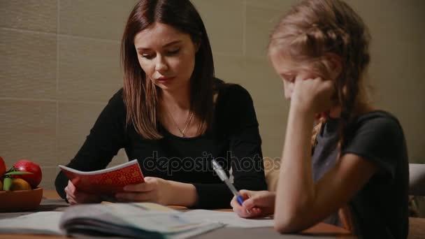 Mutter und Tochter eine Schule Hausaufgabe zu tun. Mama hilft, damit umzugehen