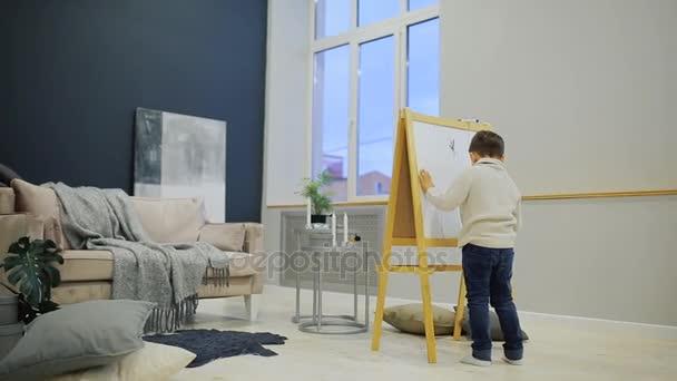Malého chlapce v obývacím pokoji domu kreslit na tabuli se značkami dětské kresby. Předškolní vzdělávání