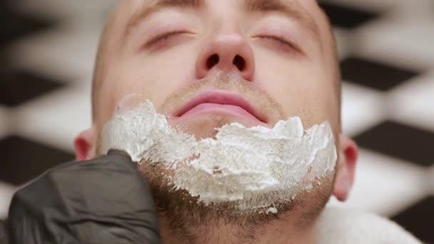 Detail obličeje člověka šíří pěnu na holení. Holič, holičství
