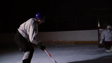 Professional hockey player produces a shot on goal at ice arena.