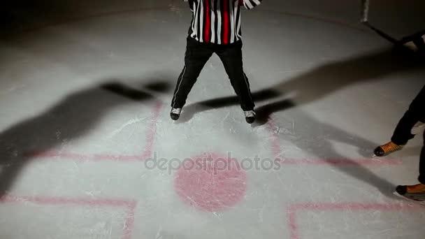 hokej rozhodčí produkuje vhazování a dva hráči začnou bojovat o PUK