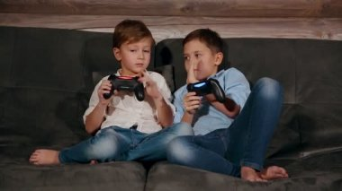 Two brothers sitting on the couch and very emotional playing video games with wireless joystick.