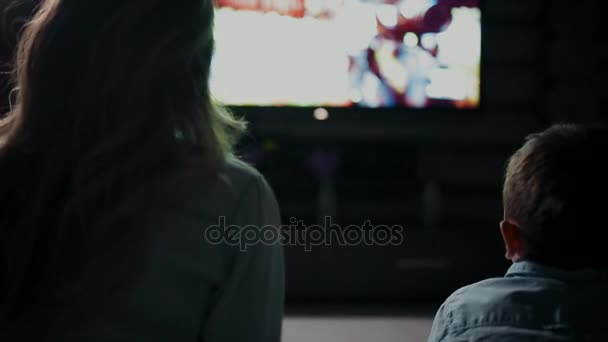Mom with son in front of the TV playing video games and pass each other the joystick. Rear view of the TV screen.