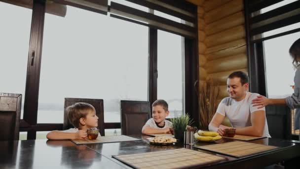 Family of four having Breakfast in his kitchen with large Windows. People are smiling, mother kissing and hugging children. Mother father and two children.