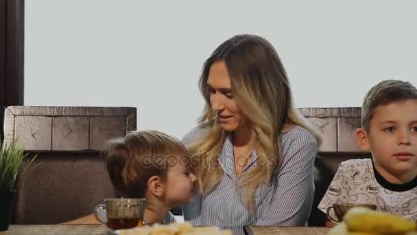 Mutter umarmt und küsst ihre Kinder zum Frühstück in der Küche. Lachende Kinder.