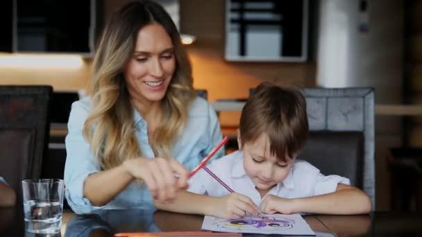 Krásná maminka pomáhá její syn Malování s pastelkami obraz. Pomáhá rozvíjet představivost dětí.