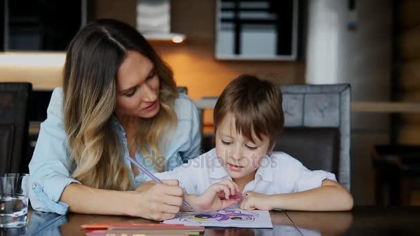 Krásná maminka pomáhá její syn Malování s pastelkami obraz. Pomáhá rozvíjet představivost dětí