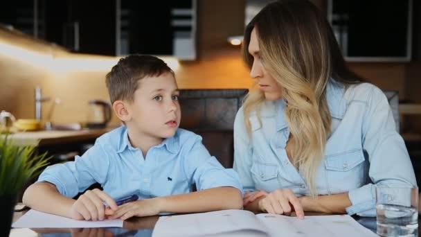 Maminka pomáhá jeho syn dělat domácí úkoly, určuje text, který má pomoci psát sedí u stolu v kuchyni.