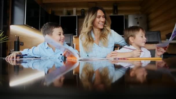 Šťastná rodina matka dvou dětí pomáhá synové dělat své domácí úkoly u velkého stolu v kuchyni