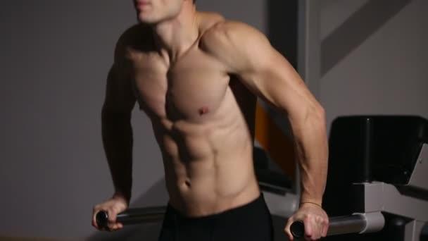 Silné silné mužské cvičení pro prsní svaly a triceps s dipy. Detail, reliéf těla.