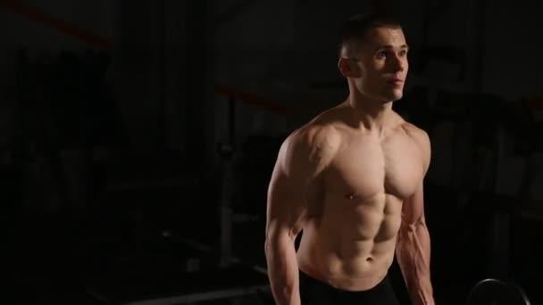 Pohledný muž s velkými svaly, pózuje v tělocvičně svalnatého muže, zvedání břemen nad tmavým pozadím svalnatý muž cvičit v tělocvičně dělat cvičení s činka na biceps silný muž. detail