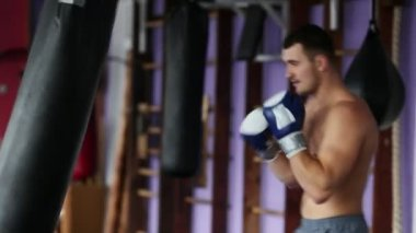 Muscular male professional boxer trains by punching bag at the gym in Boxing gloves bare-chested.