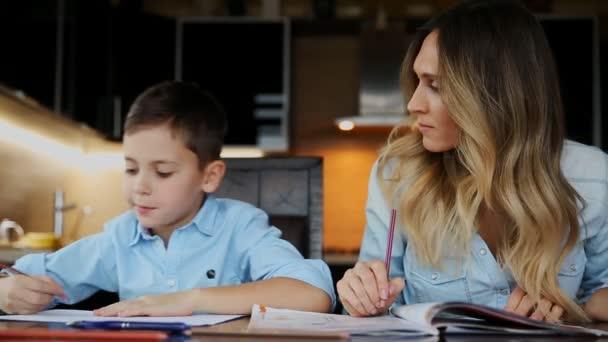 Maminka pomáhá jeho syn dělat domácí úkoly, určuje text, který má pomoci psát sedí u stolu v kuchyni