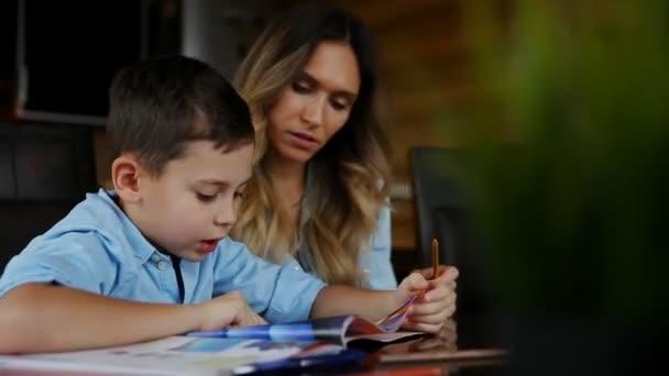Šťastná rodina matka dvou dětí pomáhá synové dělat své domácí úkoly u velkého stolu v kuchyni.