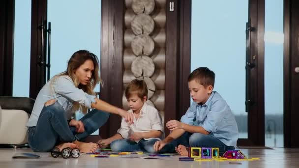 Šťastný matka s dvěma dětmi, sedí na podlaze svého domu země tráví společně čas sbírání dětské návrháře. Obývací pokoj s okny