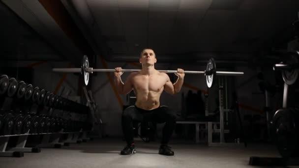 Pohledný svalnatý muž cvičení dřepy v tělocvičně