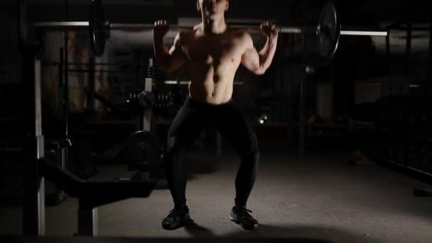 Pohledný svalnatý muž cvičení dřepy v tělocvičně.