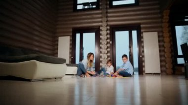 Happy mother with two children sitting on the floor of his country house spending time together collecting childrens designer. Living room with panoramic Windows.