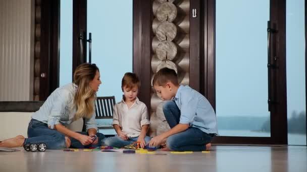 Boldog anya, két gyermek ült a földön, az ország házába tölteni az időt együtt gyűjtése gyermekek tervező. Nappali szoba panoráma ablakokkal.