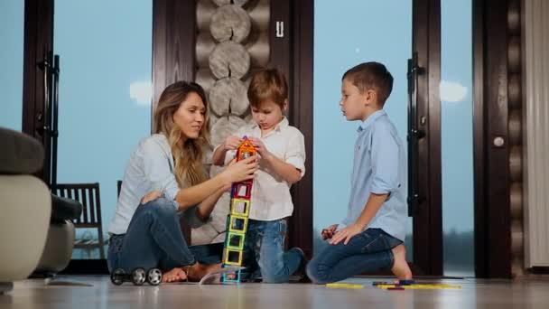 Šťastný matka s dvěma dětmi, sedí na podlaze svého domu země tráví společně čas sbírání dětské návrháře. Obývací pokoj s okny.