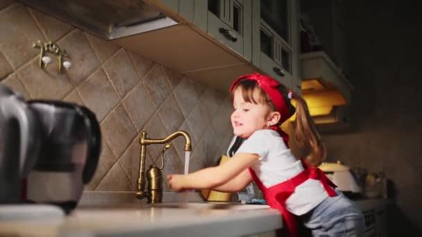 Máma pomáhá umýt ruce své dcery v kuchyni po vaření večeře